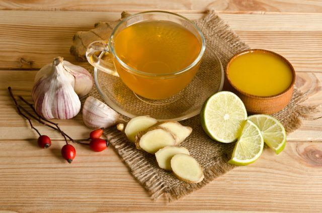 A cup of tea with lemon and garlic on a wooden table.