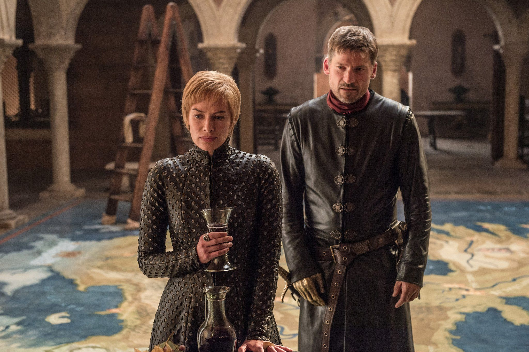Cersei holds a glass and stands next to Jaime Lannister