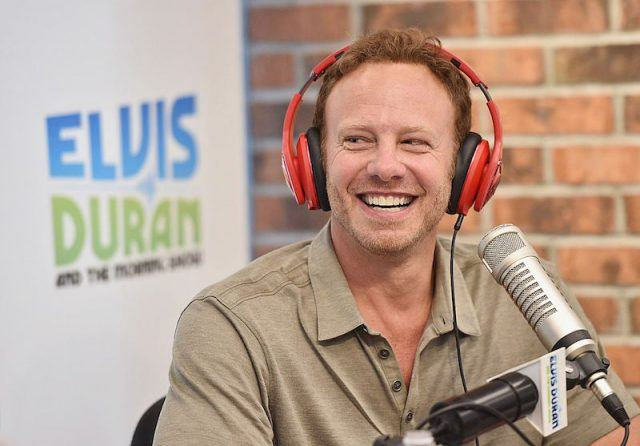 Ian Ziering smiles and wears red headphone while sitting in front of a microphone during a radio interview.
