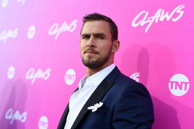 Jack Kesy poses for photos at a red carpet event wearing a blue and black suit.