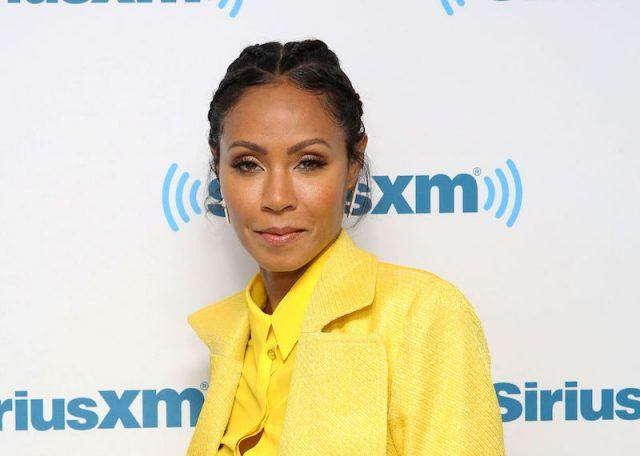 Jada Pinkett Smith wears a yellow shirt and coat and smiles while posing for photos.