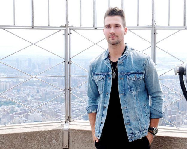 James Maslow stands in front of a city view in a denim jacket.