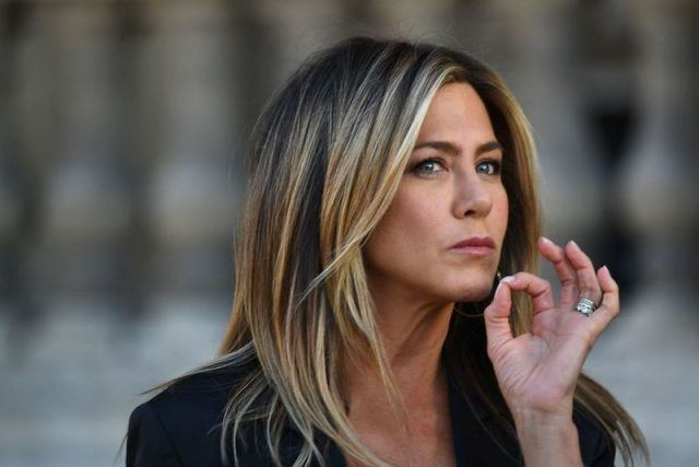 Jennifer Aniston making an OK sign with her hand.