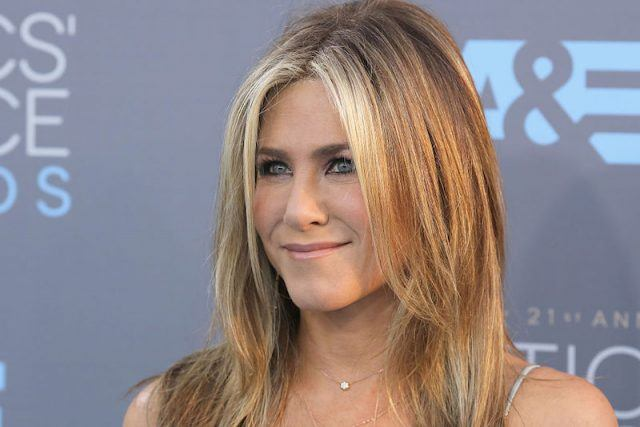 Jennifer Aniston smiles and looks upward towards photographers and a crowd.