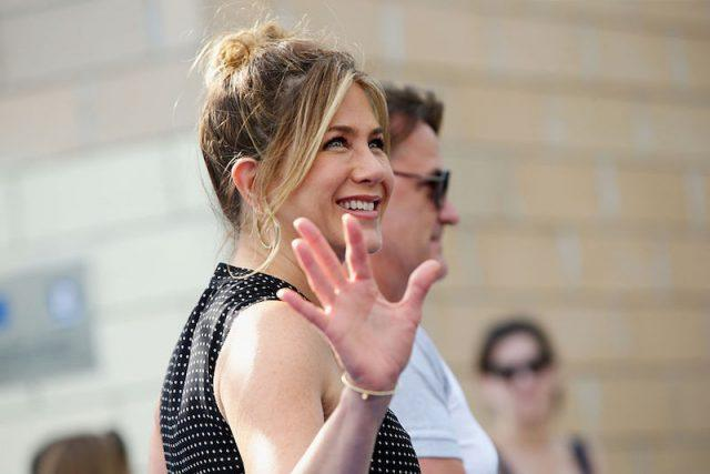 Jennifer Aniston smiles and waves at a crowd as she walks past.