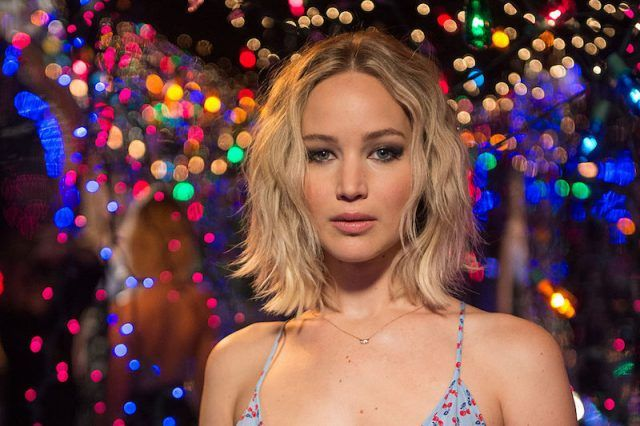 Jennifer Lawrence standing in front of colorful lights.