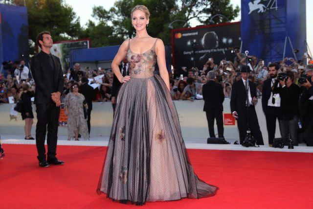 Jennifer Lawrence smiles and poses with one hand on her hip while posing for photos at the red carpet of a gala.