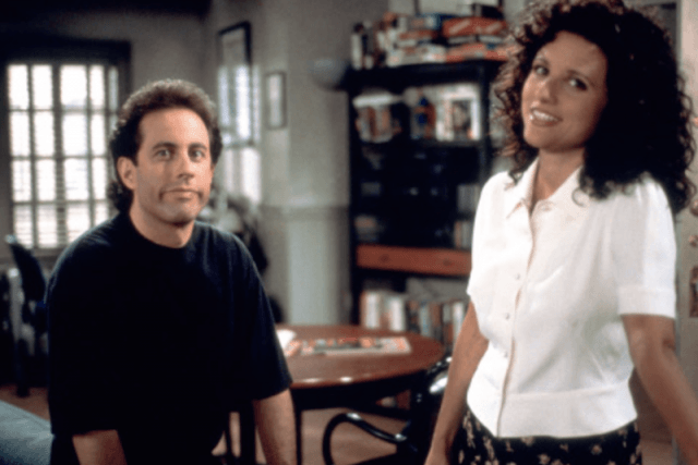 Jerry and Elaine sit in his apartment looking straight ahead and smiling.