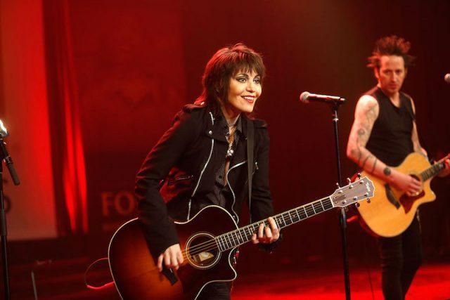 Joan Jett performing on stage with a guitar in front of a microphone.
