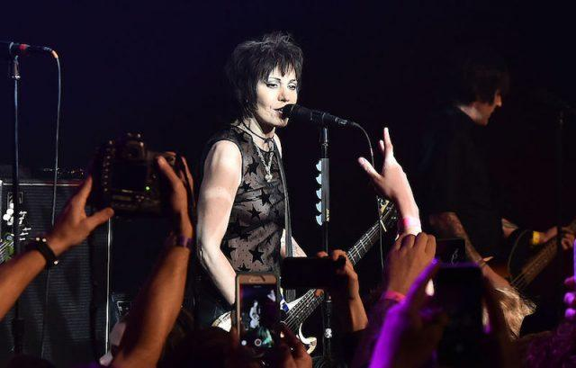 Joan Jett singing into a microphone as fans in the audience take photos.