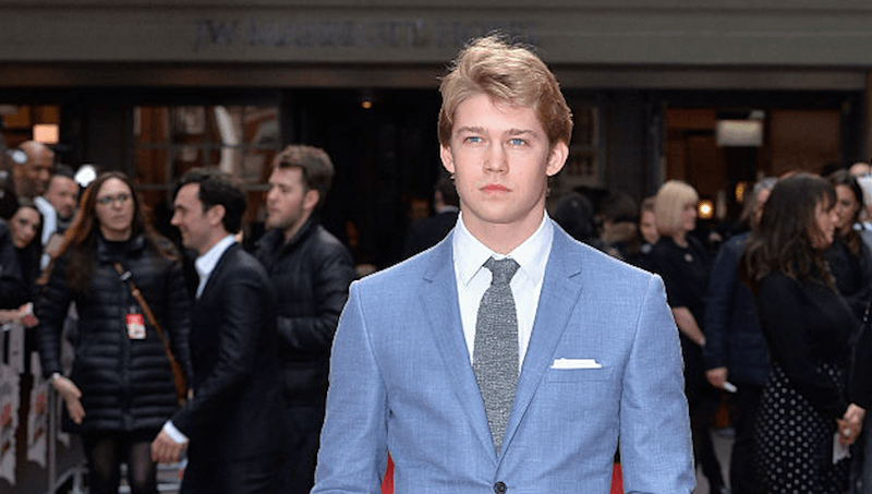 Joe Alwyn stands in a blue suit