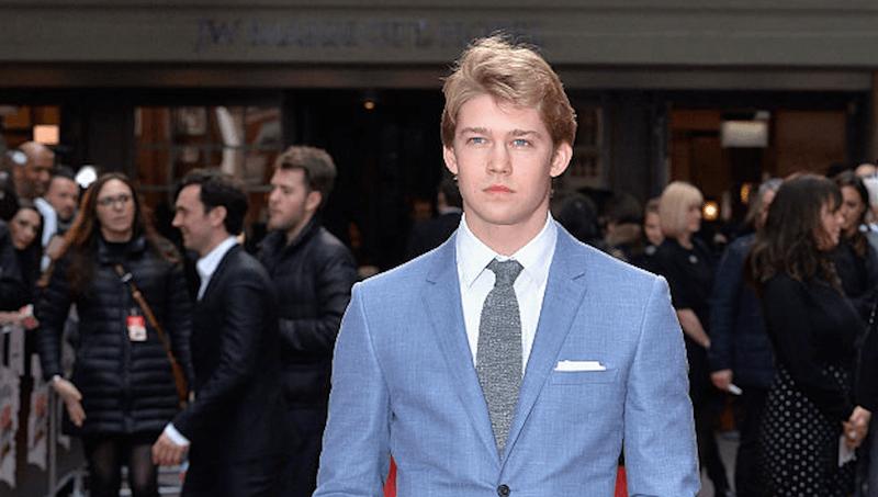 Joe Alwyn stands in a blue suit