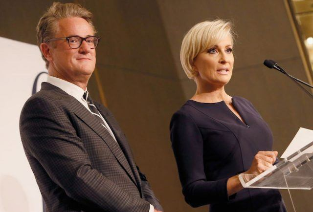 Joe and Mika stand on stage in front of a podium.