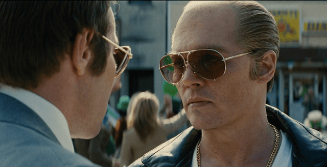 Johnny Depp in 'Black Mass', wearing shades and staring straight at John Connolly.