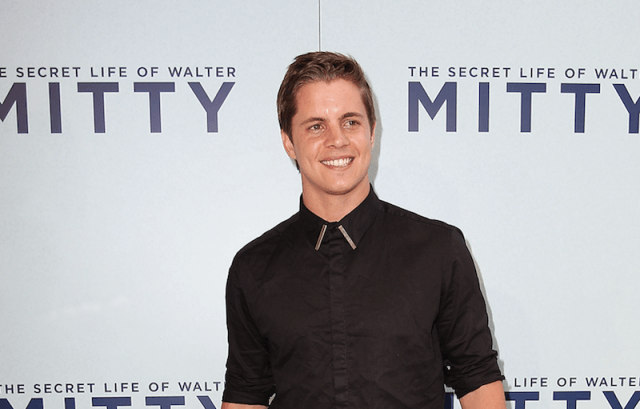 Johnny Ruffo smiles in a black shirt at an event in Australia.