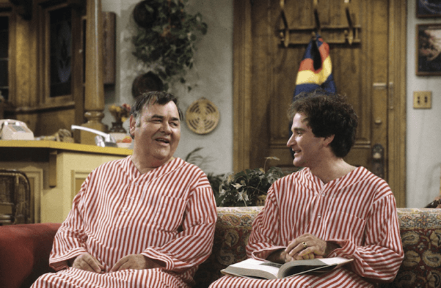 Mork and Mearth sit on a couch wearing red and white striped outfits.