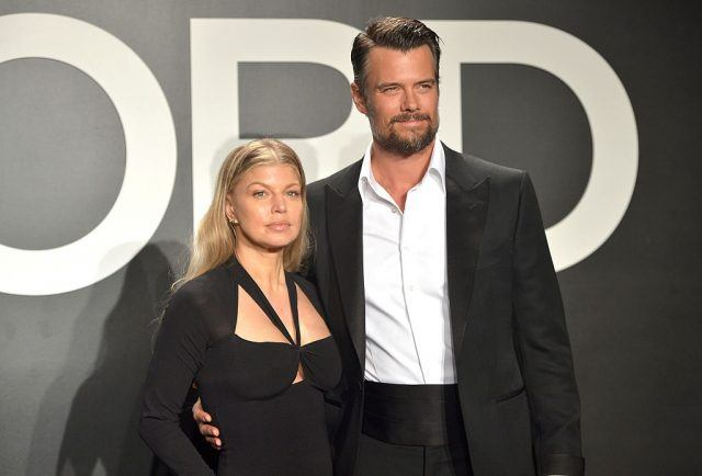 Fergie and Josh Duhamel stand together at a fashion show.