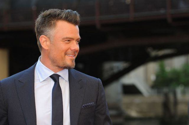 Josh Duhamel in a black striped suit turning to the side.