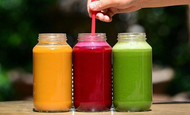 Three different juices, one with a straw in it