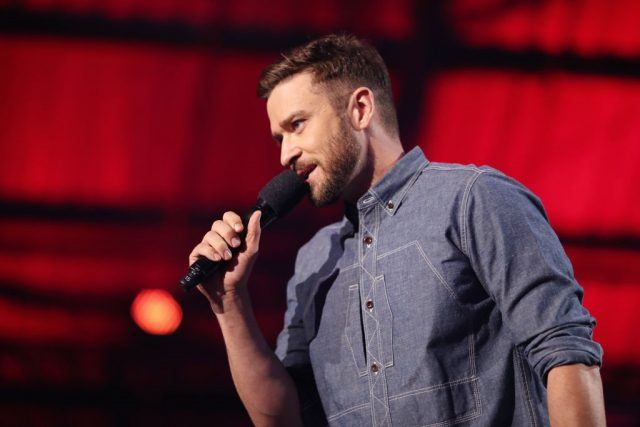 Justin Timberlake speaks into a microphone on stage.
