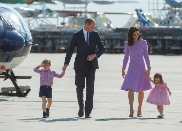 The royal family walks out of a plane wearing color coordinated clothes.