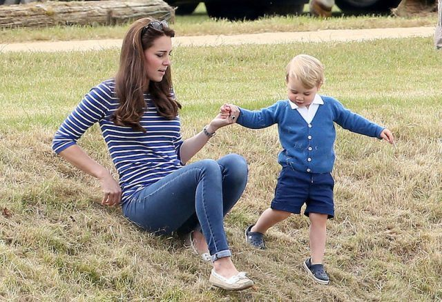 Prince George plays with his mother in a field.
