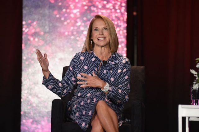 Katie Couric sits in a patterned dress on stage while speaking to an audience.