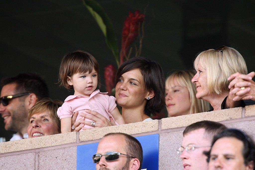 Katie Holmes holds her daughter Suri Cruise as they watch a soccer game.