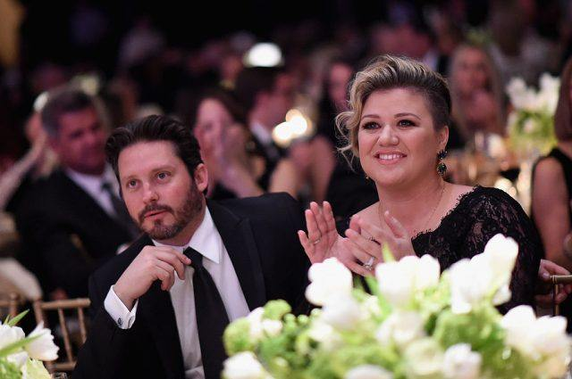 Kelly Clarkson and husband Brandon Blackstock sitting together as Brandon watches the stage and Kelly applauds.