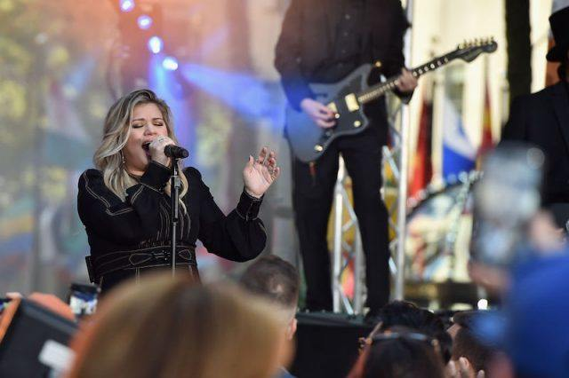 Kelly Clarkson performing in a black suit while holding a microphone in one hand.