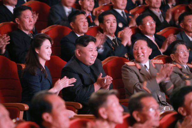 Kim Jong Un and his wife clapping their hands at a performance or service.
