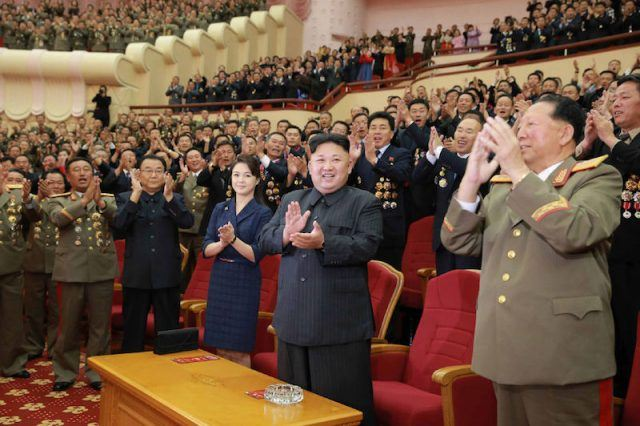 A room of North Korean Government officials surrounding Kim Jong Un and clapping vigorously.