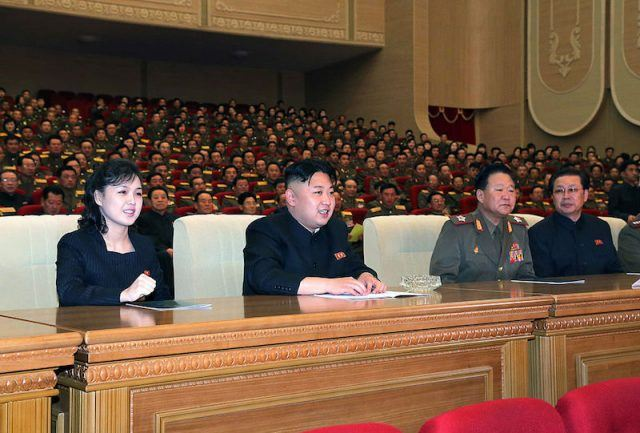 Kim Jong Un sitting with his wife at a bench.