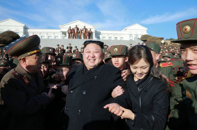 Ri Sol Ju holds Kim Jong Un's arm while walking past the military.