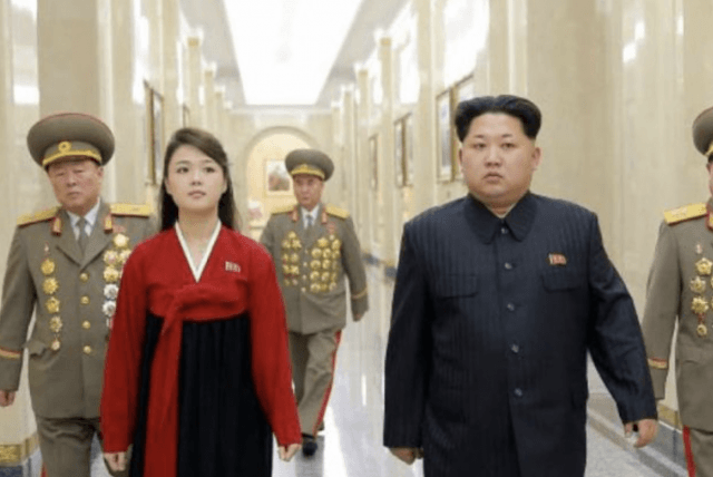 Kim Jong Un walking with his wife and military personnel.