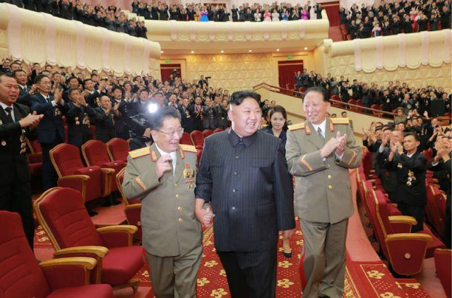 Kim Jong Un walks with two military men.