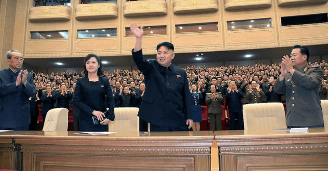 Kim Jong Un waving at guests as he stands in front of a large desk.