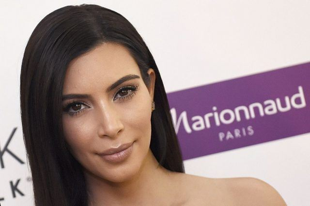 Kim Kardashian posing on a red carpet in Paris, staring straight ahead and smiling slightly.