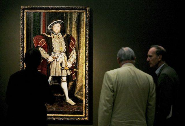 A group of men stand in front of a painting of King Henry VIII .