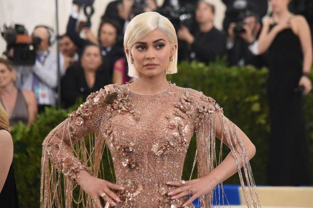 Kylie Jenner attends a gala at the Metropolitan Museum of Art and poses with her hands on her hips.