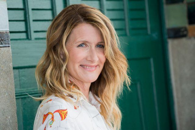 Laura Dern smiles in front of a green wall.
