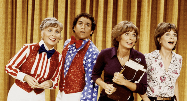 Laverne, Shirley, Edna and Carmine standing on a stage while looking outwards.