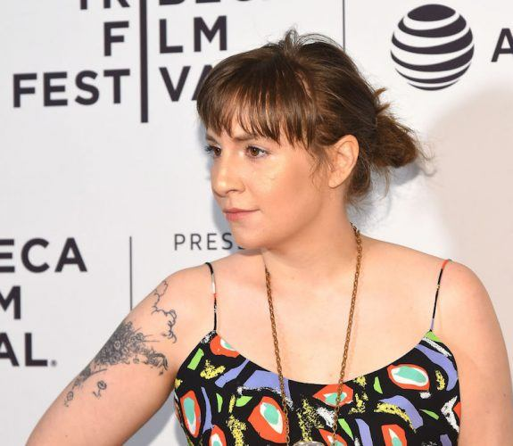 Lena Dunham poses at a red carpet event in a colorful dress and bold jewelry.