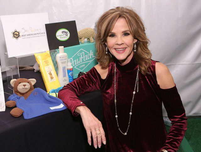 Linda Blair sits in front of a desk full of products.