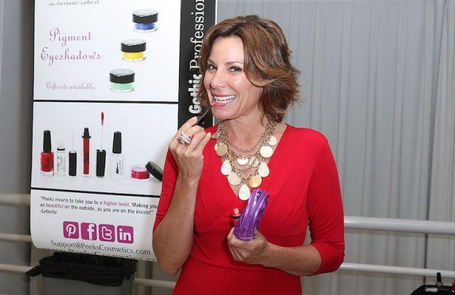 Luann de Lesseps applies a lip product while at a launch party.