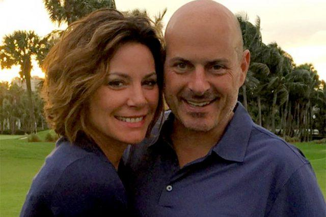 Luann and Tom pose together outside in matching shirts.