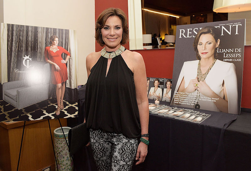 Luann de Lesseps stands in front of a table holding a poster of a magazine cover