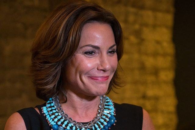 Luann de Lesseps smiles while wearing a blue necklace.