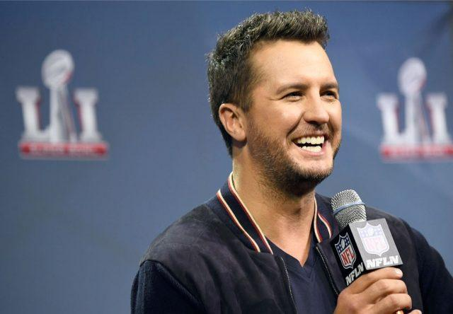 Country singer Luke Bryan speaking into a microphone.