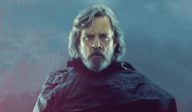Luke Skywalker stands in a dark cape in front of a gray background.